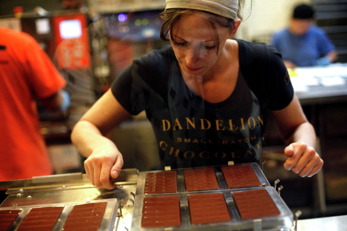 Erica Land uses a vibrating table to remove air bubbles from chocolate bars at Dandelion Chocolate in San Francisco.