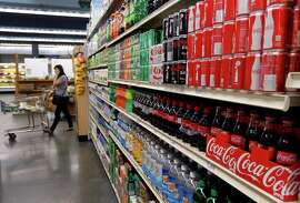 A customer walks past shelves of soft drinks at the Berkeley Bowl West market in Berkeley, Calif. on Thursday, Nov. 6, 2014. Berkeley voters overwhelmingly passed Proposition D, which will levy a one cent per ounce tax on beverages containing sugar, becoming the first city in the nation that approved a so-called sugar tax.