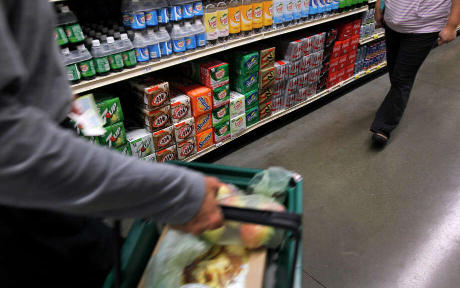 Shoppers walk past shelves of soft drinks at the Berkeley Bowl West market. The town's tax on sugary beverages passed, but few in Berkeley drink soda. Photo: Paul Chinn / The Chronicle / ONLINE_YES