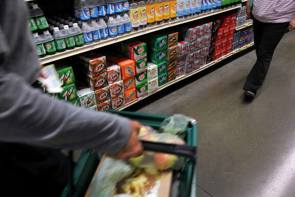Shoppers walk past shelves of soft drinks at the Berkeley Bowl West market. The town's tax on sugary beverages passed, but few in Berkeley drink soda.