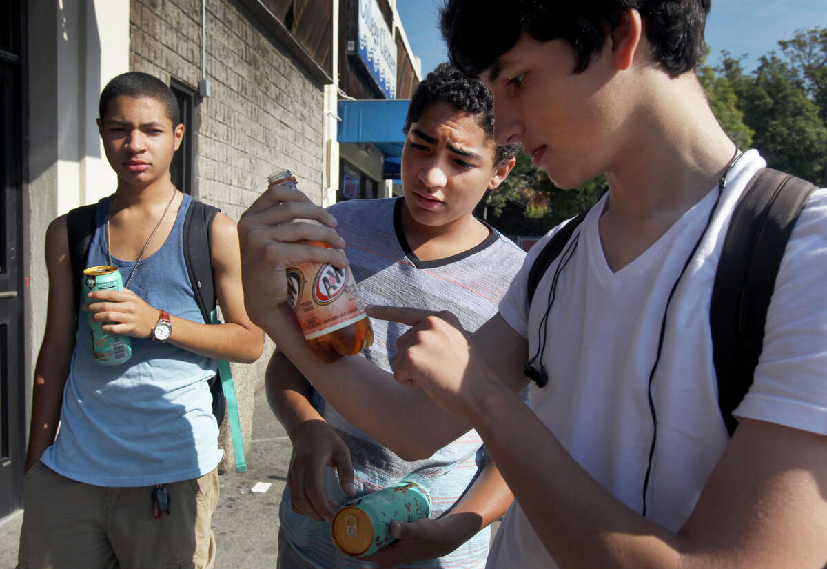Maybeck High School students Zeke Gumora (left), Baijean Shine and Rory Cooper check the sugar content of their drinks outside a 7-Eleven in Berkeley. All said that they wouldn't give up their sweet drinks no matter what the surcharge was.