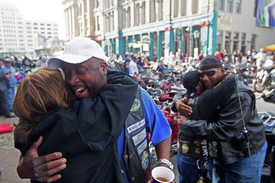 Seeing old friends, left, Marcel Johnson gives a hug to Shirlei Martins as Wayne Hollins greets Jack Daniel Jr.  on The Strand at the start of the Lone Star Rally.   Photo: Johnny Hanson, Staff / © 2014  Houston Chronicle