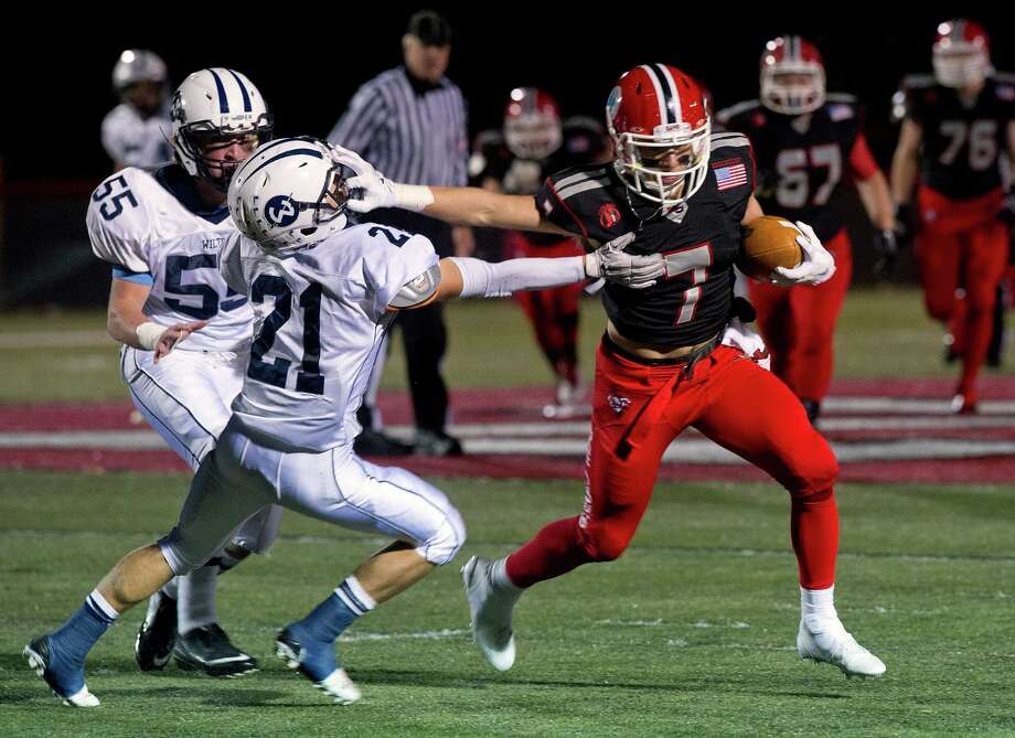 New Canaan's Alex LaPolice avoids a tackle by Wilton's Patrick Ryan and runs for a touchdown during Friday's football game at New Canaan High School on November 7, 2014. Photo: Lindsay Perry / Stamford Advocate