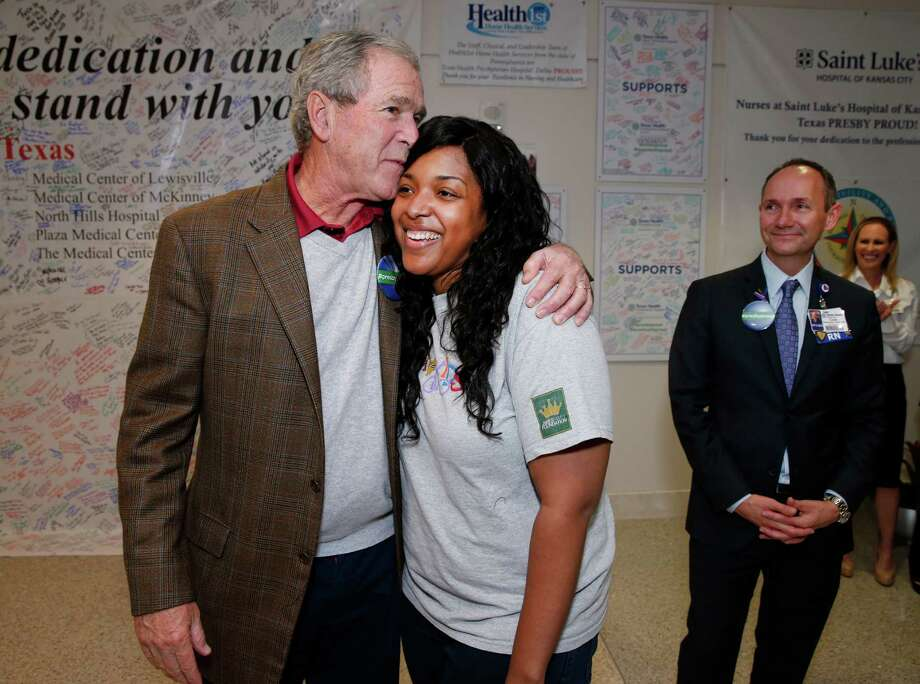 Amber Vinson, a nurse who was infected with Ebola after treating a sick patient, gets a hug from former President George W. Bush on Friday, the day on which Dallas marked the end of its Ebola crisis as the last people being monitored for symptoms were to be cleared at midnight. Photo: David Woo, MBR / The Dallas Morning News