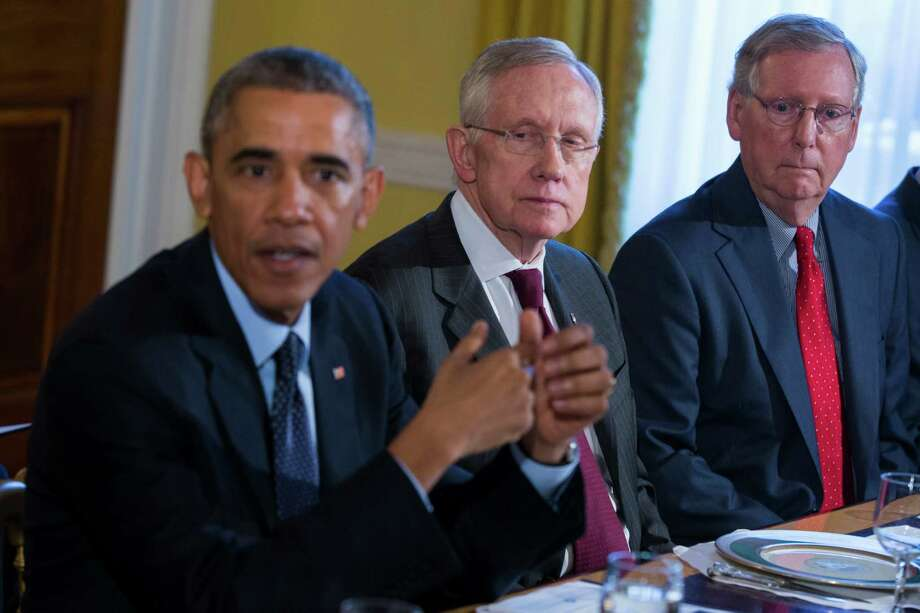 Senate Minority Leader Mitch McConnell of Ky., right, and Senate Majority Leader Harry Reid of Nev., center, listen as President Barack Obama speaks during a meeting with Congressional leaders in the Old Family Dining Room of the White House in Washington, Friday, Nov. 7, 2014. (AP Photo/Evan Vucci) ORG XMIT: DCEV114 Photo: Evan Vucci / AP
