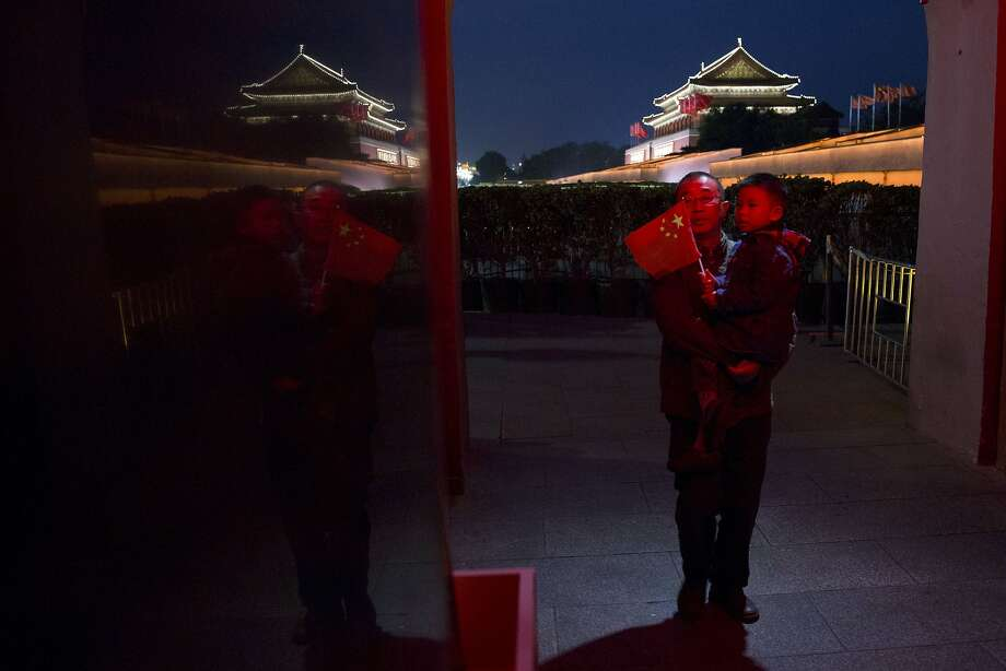 A man carries a child near Tiananmen Gate in Beijing, China, Friday, Nov. 7, 2014. Despite earlier estimates that new exemptions to China's one-child policy would add up to 2 million extra births per year, only 700,000 newly qualified couples applied to have a second child this year, a Chinese official said this week. (AP Photo/Ng Han Guan) Photo: Ng Han Guan, Associated Press