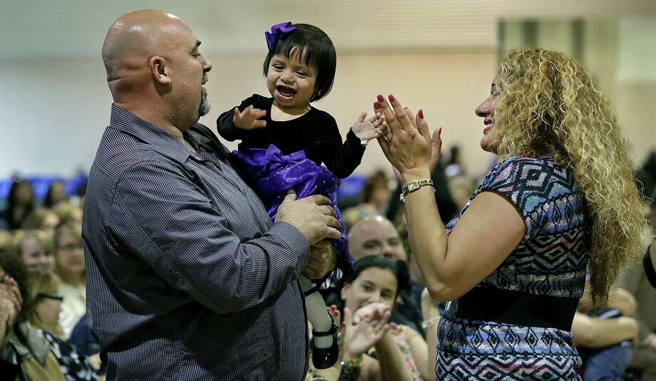 Liliana Faith Galvan celebrates with her new mother Monica Galvan and father Jammeth Galvan as their names are called during a mass ceremony where 88 children were adopted. Photo: Photos By Bob Owen / San Antonio Express-News / © 2014 San Antonio Express-News