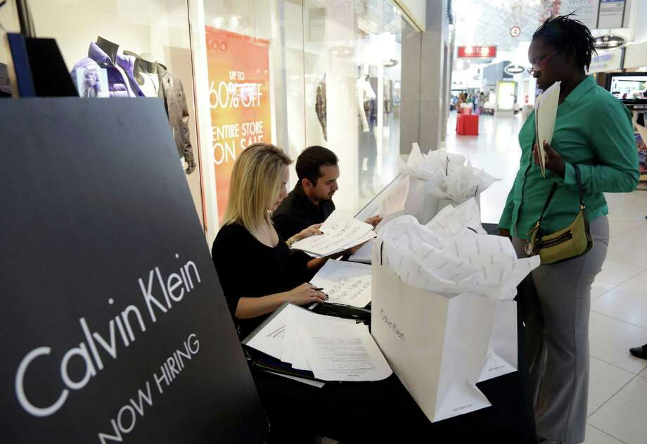 In this Oct. 28, 2014 photo, Shantel Howard, 29, of Miami, right, makes an appointment for a job interview with Calvin Klein employee Melina Mikhalices, left, after submitting her resume during a job fair at Dolphin Mall, in Miami. The Labor Department releases employment data for October on Friday, Nov. 7, 2014. (AP Photo/Lynne Sladky) Photo: Lynne Sladky, STF / AP