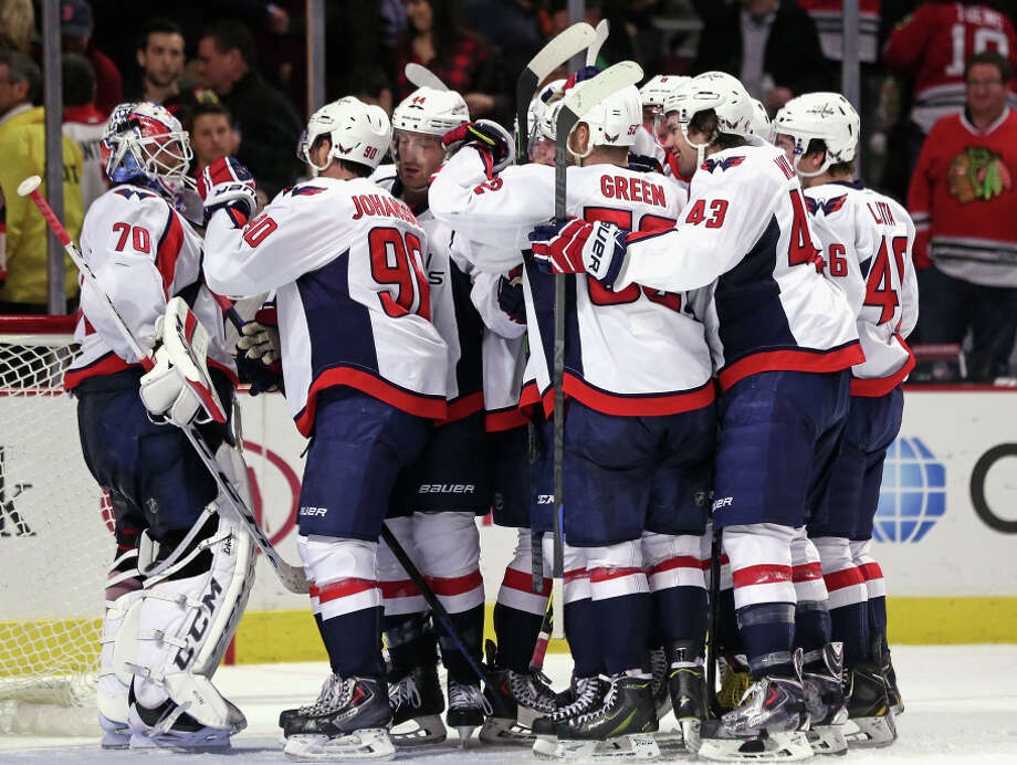 Players converge on goalie Braden Holtby after the Capitals ended a five-game losing streak with a win in Chicago. Photo: Jonathan Daniel / Getty Images / 2014 Getty Images
