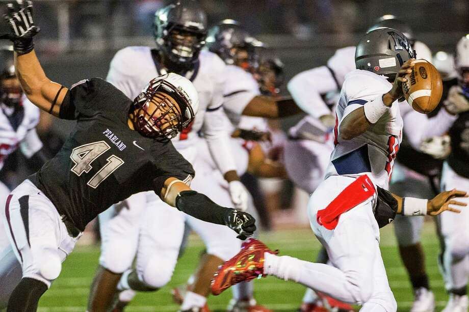 Manvel quarterback D'Eriq King (10) gets past Pearland defensive end Deonte Givens (41) during the second half of the Mavericks' win Friday night at The Rig. Photo: Smiley N. Pool, Staff / © 2014  Houston Chronicle