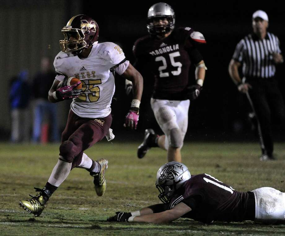 Magnolia West's Aaron Thomas, left, scampers by Magnolia defensive back Benton Ashe for a 62-yard touchdown run that lifted the Mustangs to victory and into the playoffs for the fifth consecutive year. Photo: Eric Christian Smith, Freelance / 2014 Eric Christian Smith