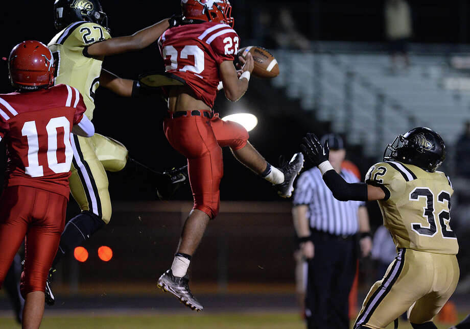 Kountze's Deontra Morgan leaps to complete the pass against the pressure of Anahuac during Friday's game at Kountze High School. Photo taken Friday, November 7, 2014 Kim Brent/@kimbpix Photo: KIM BRENT / Beaumont Enterprise