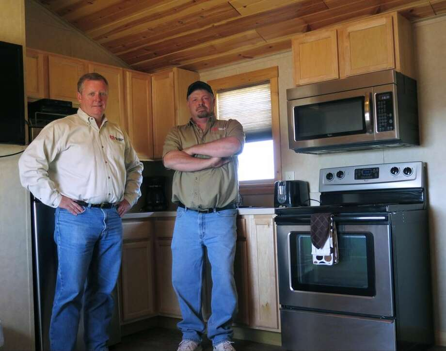 Reliant Asset Management Executive Vice President Peter Eberle and camp manager Shawn Duby are seen in a cabin at a hybrid man camp near Watford City, North Dakota in this Sept. 23, 2014 photo. The Watford City complex provides workers more private accommodations with shared living spaces _ something that makes the cabins feel a lot more like home than the long metal hallways of a traditional man camp. (AP Photo/Josh Wood)