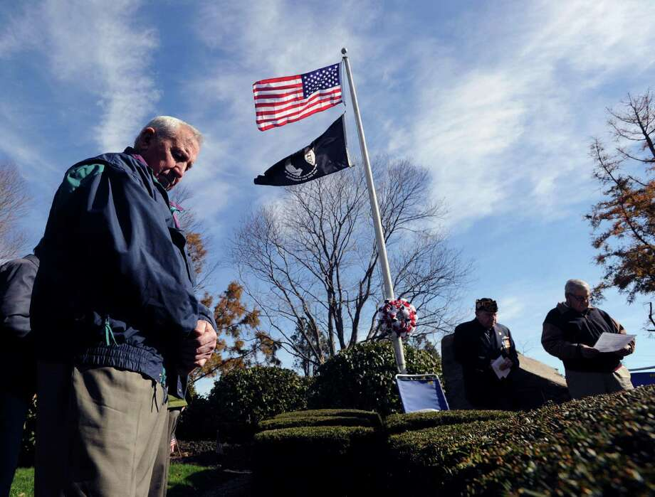 At left, Riverside resident, Graziano Bortot, a Vietnam Veteran who served in the U.S. Army, bows his head during the Cos Cob VFW Post 10112  Veterans Day ceremony at the Cos Cob Veterans of Foreign Wars Memorial on Strickland Road in Cos Cob, Conn., Saturday, Nov. 8, 2014. Photo: Bob Luckey / Greenwich Time
