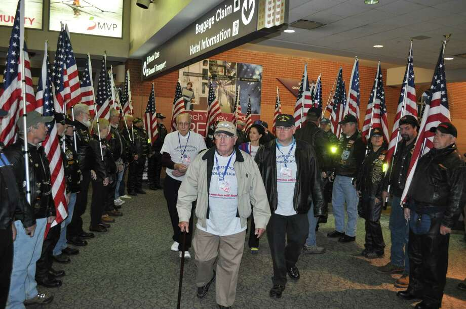 Neil Taber, 88, Altamont, N.Y. (center) passes through the Patriot Riders honor guard Saturday, Nov. 8, 2014, on his way to board the Leatherstocking Honor Flight. Taber served with the Army Air Corps during World War II. (Doug Myers/Albany International Airport)
