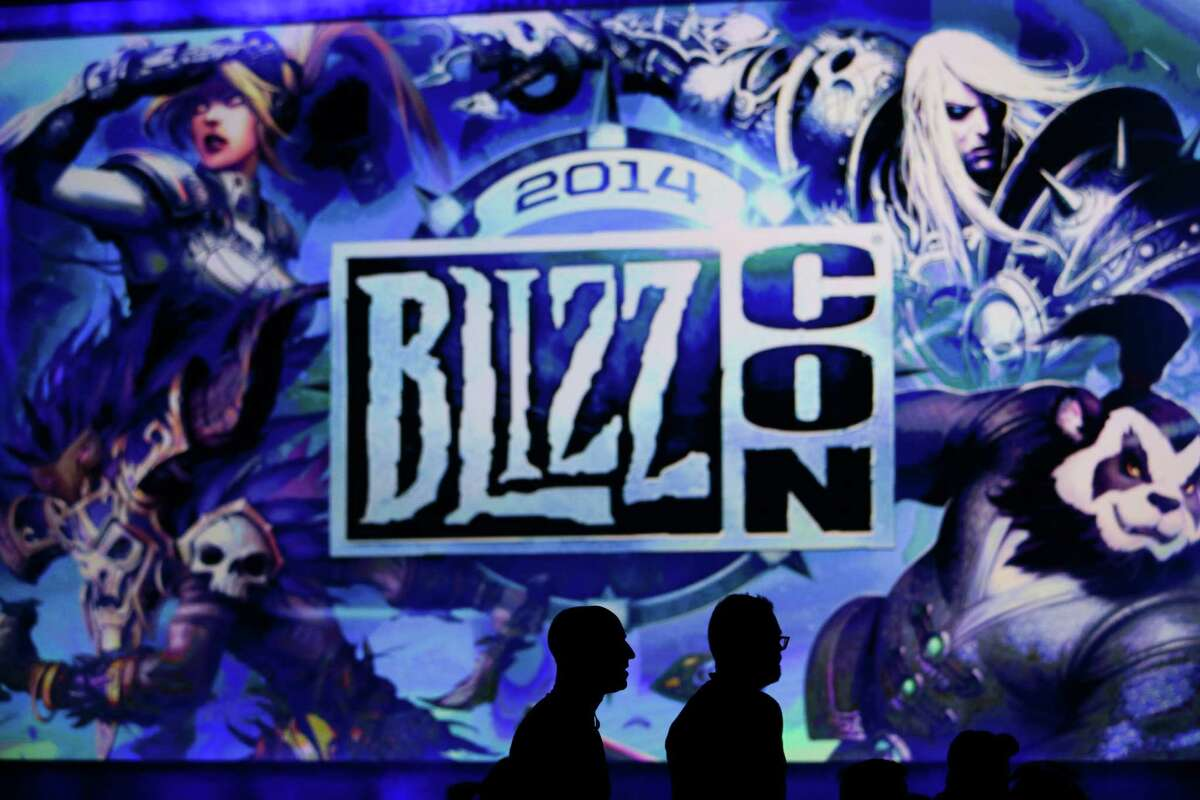 Two attendees are silhouetted as they wait for the opening ceremony at the BlizzCon, the fan-centric celebration of video game publisher Blizzard, Friday, Nov. 7, 2014, in Anaheim, Calif. The annual convention kicked off Friday with more than 25,000 attendees. (AP Photo/Jae C. Hong)