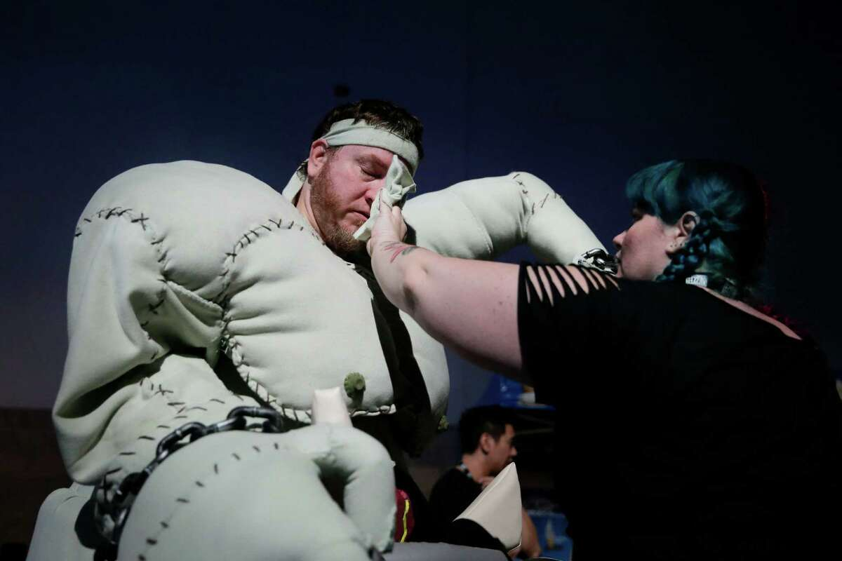 Theresa Murphy, right, wipes the sweat from the face of her boyfriend, Dan Miller, who dressed as a game character at the BlizzCon, the fan-centric celebration of video game publisher Blizzard, Friday, Nov. 7, 2014, in Anaheim, Calif. The annual convention kicked off Friday with more than 25,000 attendees. (AP Photo/Jae C. Hong)