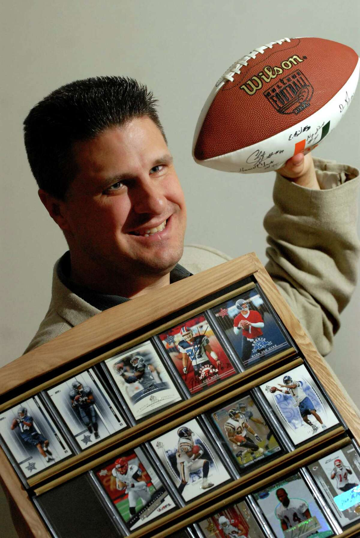Local NFL agent J.R. Rickert poses with a football and collection of football player cards in his Niskayuna home in 2006. (Cindy Schultz / Times Union) ORG XMIT: MER2014110714354488