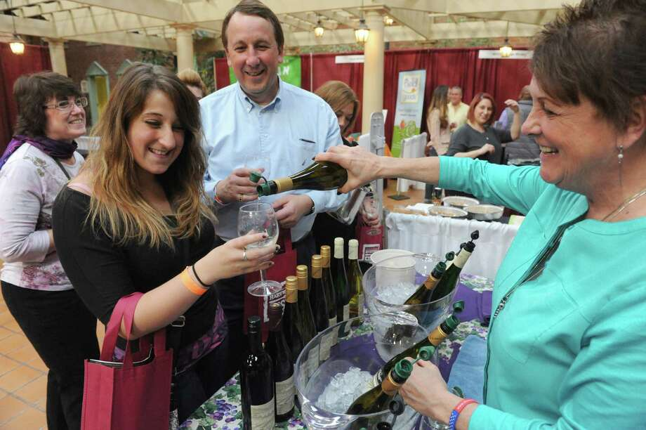 Amy Tedesco, left,of Rotterdam, left, and her father Jeff Tedesco sample wine from the Dr. Konstantin Frank Winery poured by sales representitive Susan Eisenhart during the Pride of New York Harvest and Wine Festival at the Desmond Hotel on Saturday Nov. 8, 2014 in Colonie, N.Y. (Michael P. Farrell/Times Union) Photo: Michael P. Farrell / 00029414A