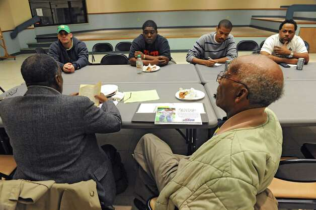 "Community Fathers founder Walter Simpkins reads from the book ""The Greatest Salesman in the World: Part II-The End of the Story"" to men during a program at the Steinmetz Family Investment Center on Thursday, Oct. 30, 2014 in Schenectady, N.Y. The program is put on by the Community Fathers and helps troubled fathers, some of them ex-felons and others dealing with domestic violence problems. (Lori Van Buren / Times Union) Photo: Lori Van Buren / 00029262A"