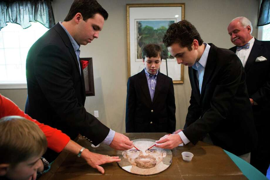 From left, John McDavid V, 16, and his siblings, Thomas McDavid, 12, and Nicholaus McDavid, 14, lay a coat of glue on a portrait of their father, John Carlisle McDavid IV, whose organs were donated after his death in 2013. The portrait is among 70 to be featured in Pasadena's Rose Parade in January. Photo: Marie D. De Jesus, Staff / © 2014 Houston Chronicle