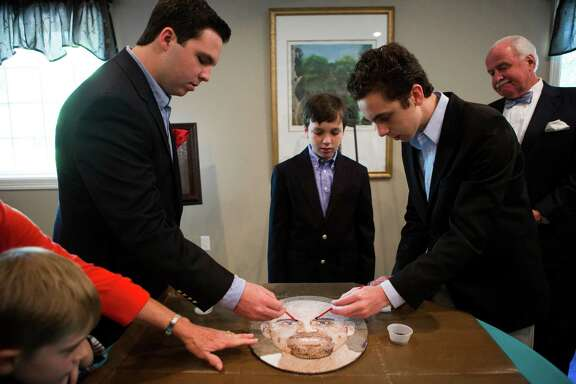 From left, John McDavid V, 16, and his siblings, Thomas McDavid, 12, and Nicholaus McDavid, 14, lay a coat of glue on a portrait of their father, John Carlisle McDavid IV, whose organs were donated after his death in 2013. The portrait is among 70 to be featured in Pasadena's Rose Parade in January.