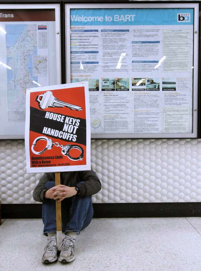 A man, who identified himself only as Eddie, sits down with dozens of other demonstrators inside the Powell Street BART station in San Francisco, Calif. on Saturday, Nov. 8, 2014 to protest the transit agency's crackdown on the homeless sitting or lying inside the station. Photo: Paul Chinn / The Chronicle / ONLINE_YES