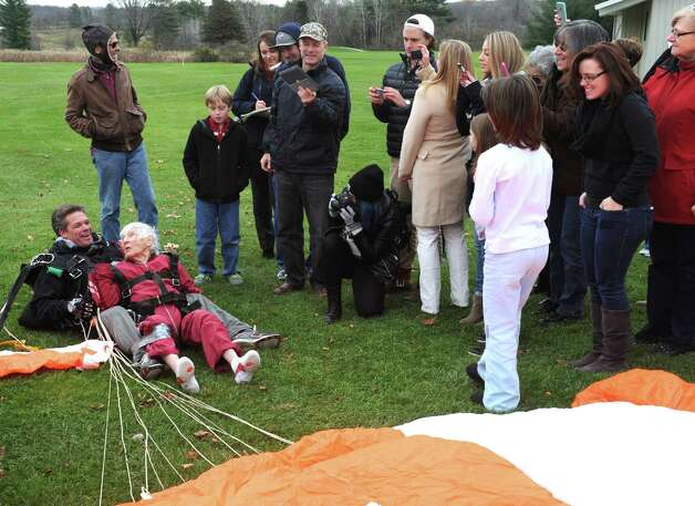 """One-hundred-years-young Eleanor """"Nanny"""" Cunningham, left, with co-parachuter Dean McDonald are welcomed by Cunningham's freinds and family after her skydive on Saturday Nov. 8, 2014 in Gansevoort, N.Y. (Michael P. Farrell/Times Union) Photo: Michael P. Farrell / 00029372A"""