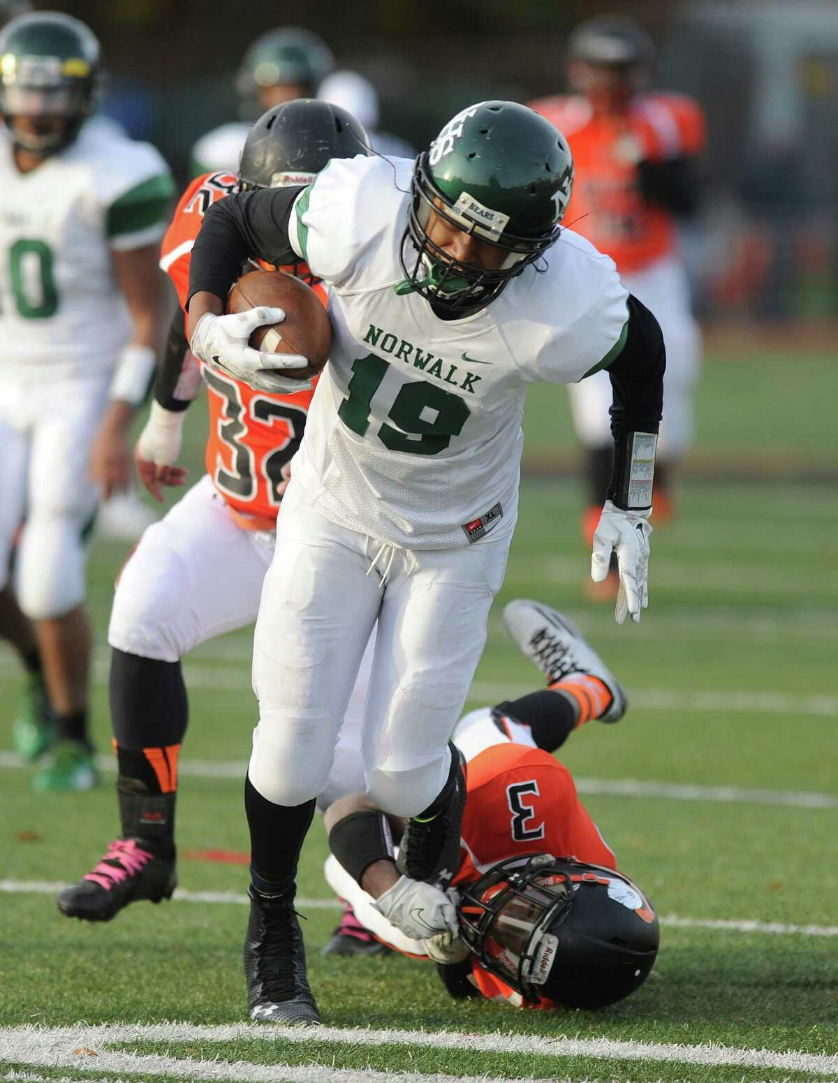 Norwalk's Izaiah Sanders escapes the grasp of Stamford's Tyree Smith during Saturday's football game on November 8, 2014, at Stamford High School.