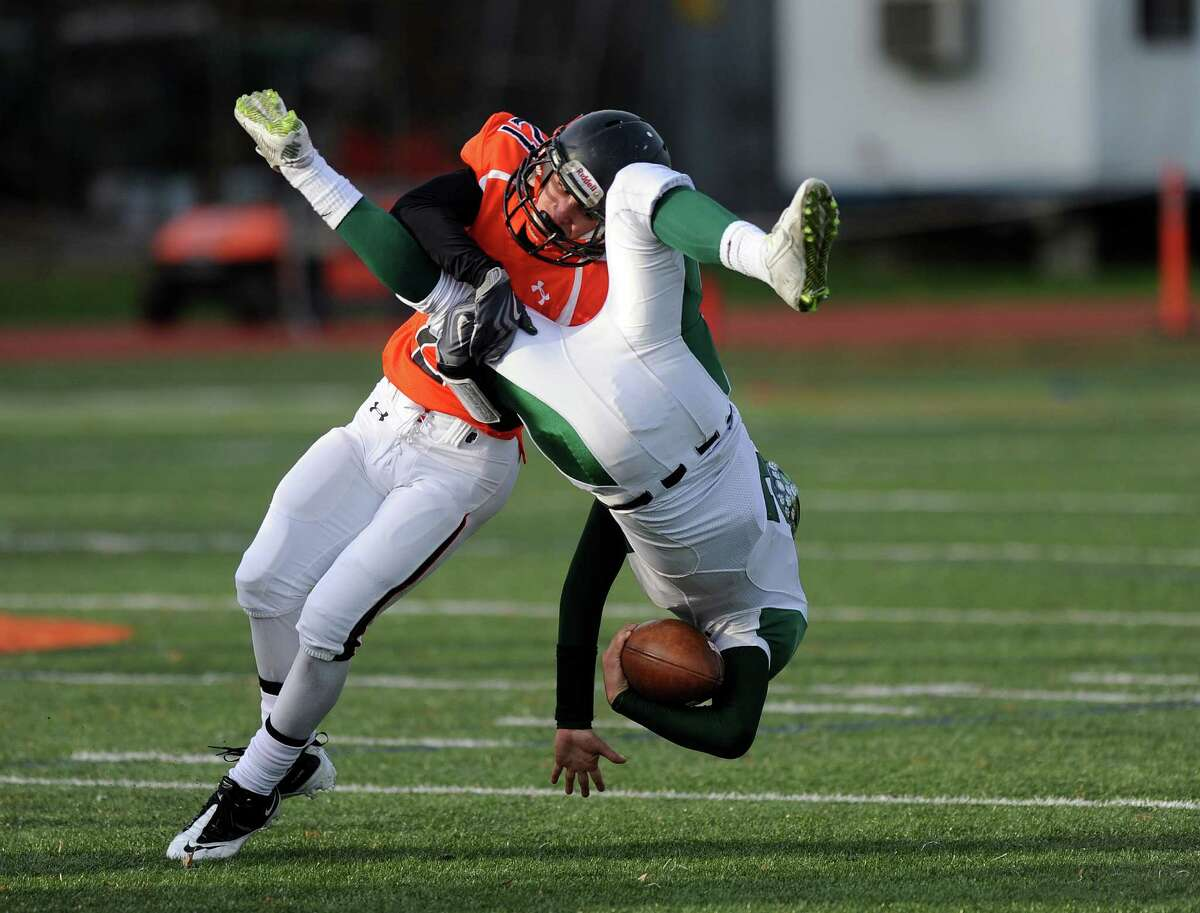 Norwalk's Harrison Hefferan flips as he is tackled by Stamford's Mark Serricchio during Saturday's football game on November 8, 2014, at Stamford High School.