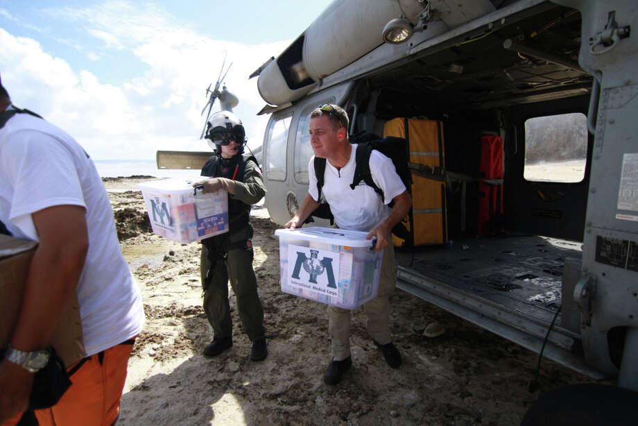 Dr. Robert Fuller (right), chief of emergency medicine at the University of Connecticut Health Center, exits a helicopter with medical supplies in Hermani, Philippines, after the November 2013 typhoon. Faced with a possible three weeks of quarantine at the end of a six week commitment, Fuller will not go to West Africa in 2014 to help with care for Ebola patients. Photo: Margaret Aguirre / Associated Press / International Medical Corps