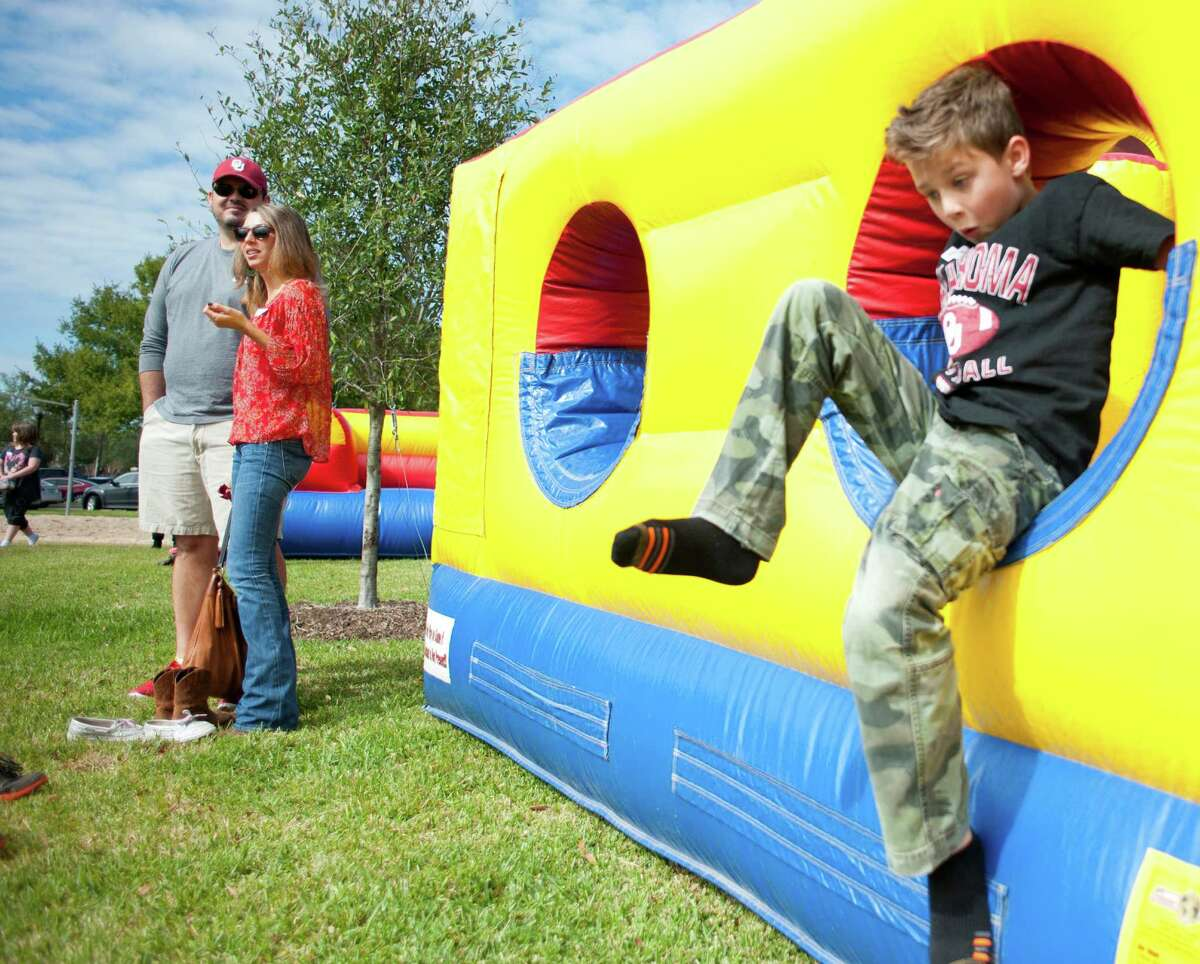Everett Morrison, 7, plays in an inflatable obstacle course while his parents Brian and Leslie Morrison watch other children with Texas Child Protective Services at an adoption festival sponsored by the Pearland Rotary on Saturday, Nov. 8, 2014 at the Silverlake Clubhouse in Pearland, Texas. The Morrisons said they always wanted to adopt a child and are looking to find one or two siblings to raise with their two biological children.
