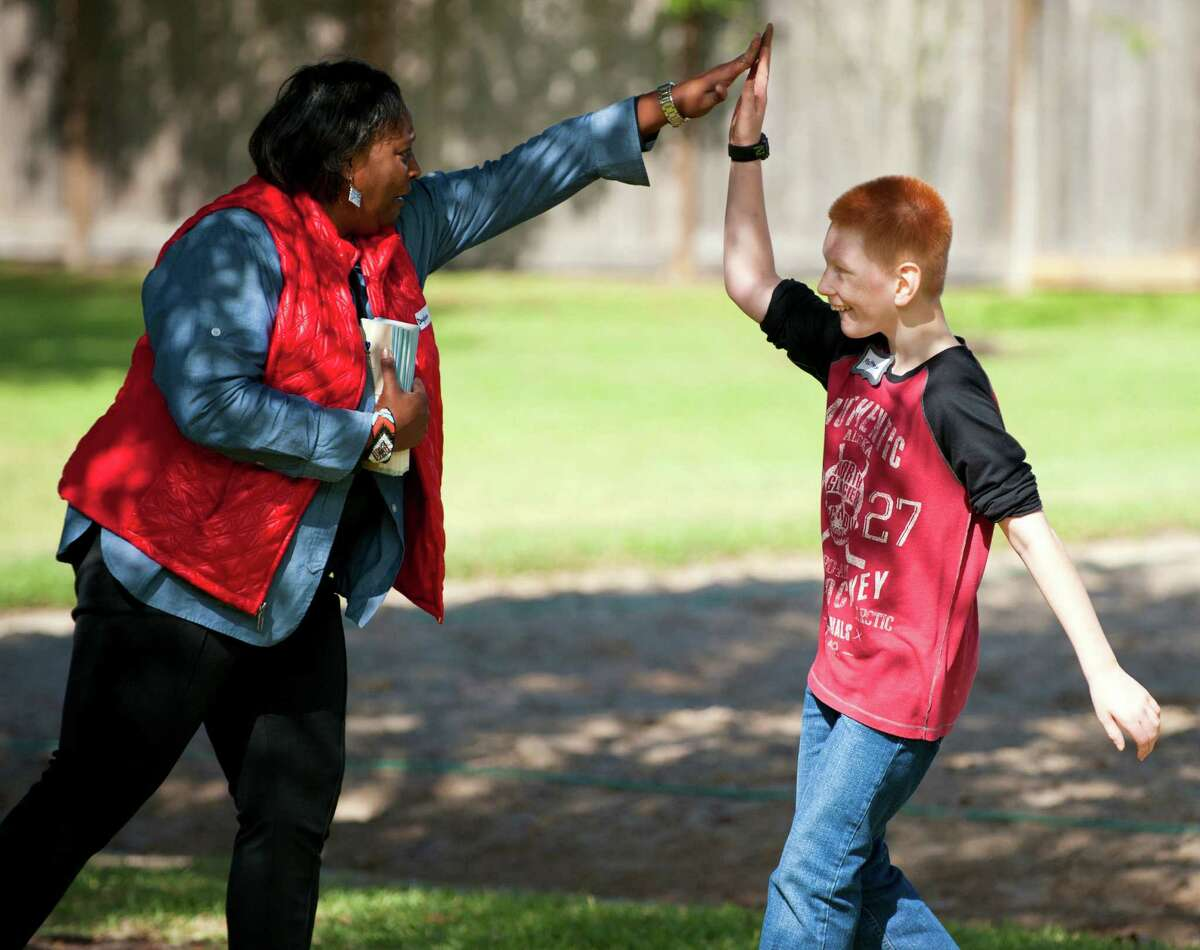 Matthew, 12, high fives Daphne McCadney with Texas Child Protective Services at an adoption festival sponsored by the Pearland Rotary on Saturday, Nov. 8, 2014 at the Silverlake Clubhouse in Pearland, Texas. Matthew and about 19 other children available for adoption were at the event along with prospective adoptive parents.