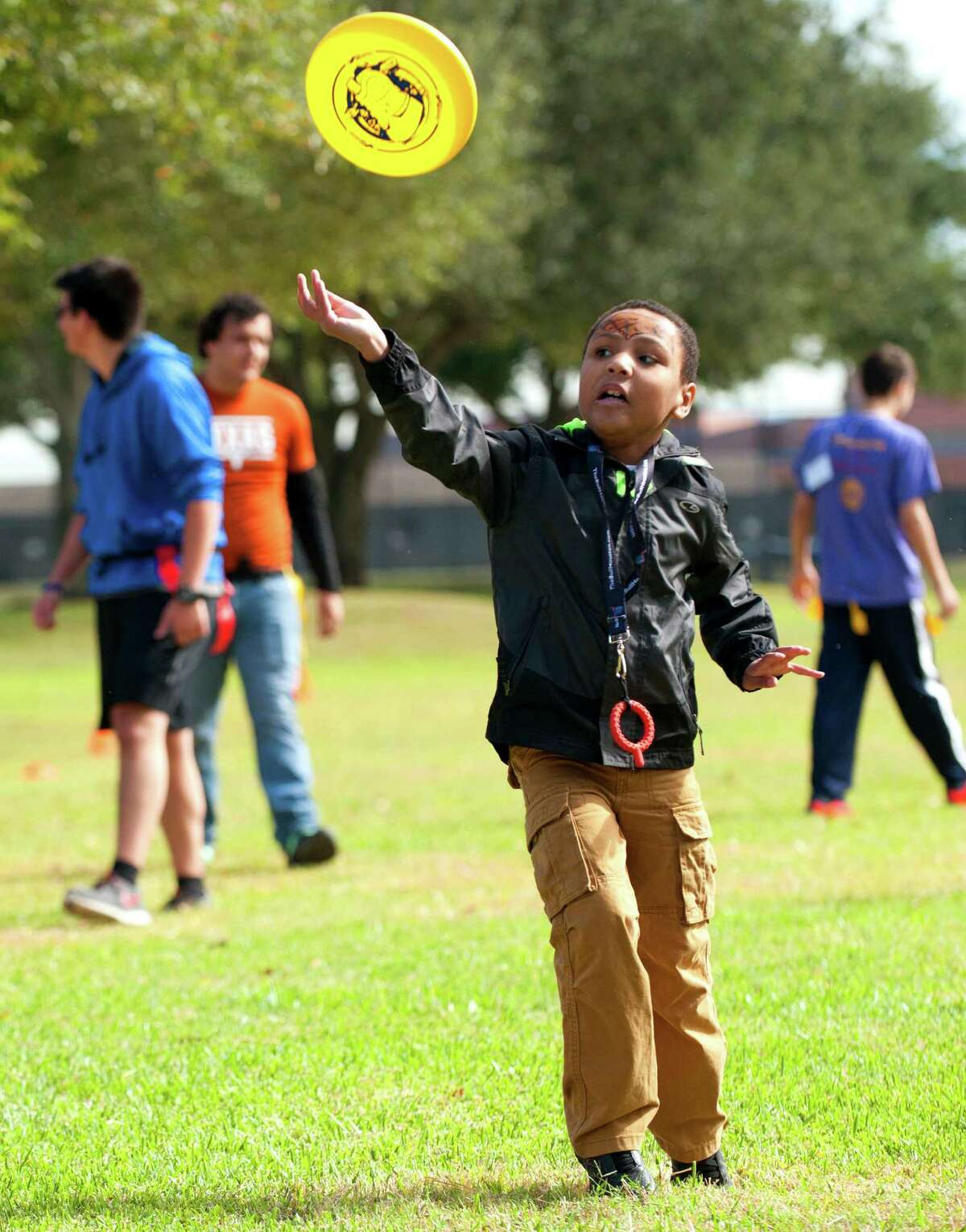 Cameron, 6, tosses a disc while playing with other children in Texas Child Protective Services at an adoption festival sponsored by the Pearland Rotary on Saturday, Nov. 8, 2014 at the Silverlake Clubhouse in Pearland, Texas. The event was part of National Adoption Month.