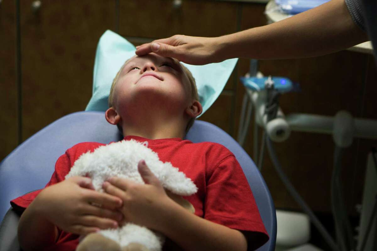 Seth Skaggs, 6, a special needs patient, finds comfort in holding a stuffed animal as pediatric dentist Amy Luedemann-Lazar helps him gradually work up to having his teeth cleaned without restraint or sedation.