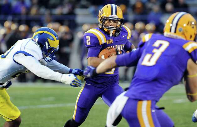 UAlbany's Josh Gontarek, center, carries the ball as Delaware's Donte Raymond, left, moves in for the tackle during their football game on Saturday, Nov. 8, 2014, at Bob Ford Field in Albany, N.Y. (Cindy Schultz / Times Union) Photo: Cindy Schultz / 00029366A