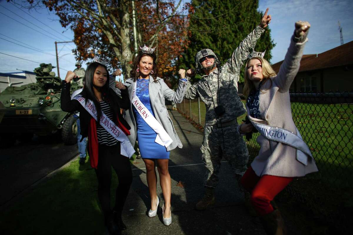 U.S. Army Sgt. Sean Rowell poses for a photo with, from left, Vivian Dao, Miss Auburn Outstanding Teen, Jacque Guyette, Miss Auburn, and Kailee Dunn, Miss Washington, during the 49th annual Auburn Veterans Day Parade.