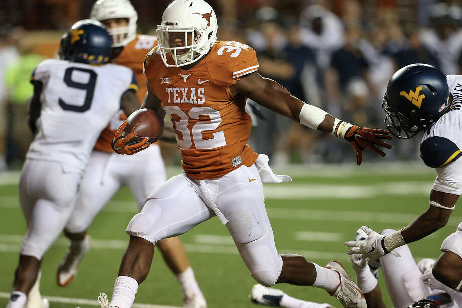 Johnathan Gray slips in for a fourth quarter touchdown as Texas hosts West Virgina at Royal Memorial STadium on Saturday. Texas upset No. 23 West Virginia 33-16. Photo: TOM REEL / TOM REEL /