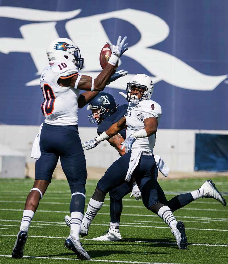 UTSA safety Brian King (10) intercepts a pass intended for Rice wide receiver Mario Hull (1) as cornerback Crosby Adams III (4) looks on during the first quarter of a college football game at Rice Stadium on Saturday in Houston. Photo: Smiley N. Pool / Smiley N. Pool / Houston Chronicle / © 2014  Houston Chronicle