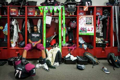 Pearland's Dwayne Williams sits among lockers covered with homecoming decorations. Before coach Tony Heath and his staff turned the program around, the locker room was devoid of the trappings of success.