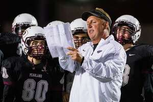 At left, Pearland offensive coordinator Mike Norman works the Oilers' game against Manvel from the coaches' booth Friday night. At right, Pearland coach Tony Heath gathers his players on the field before the game against Manvel. The Mavericks edged the Oilers 35-33 to claim the District 22-6A championship.