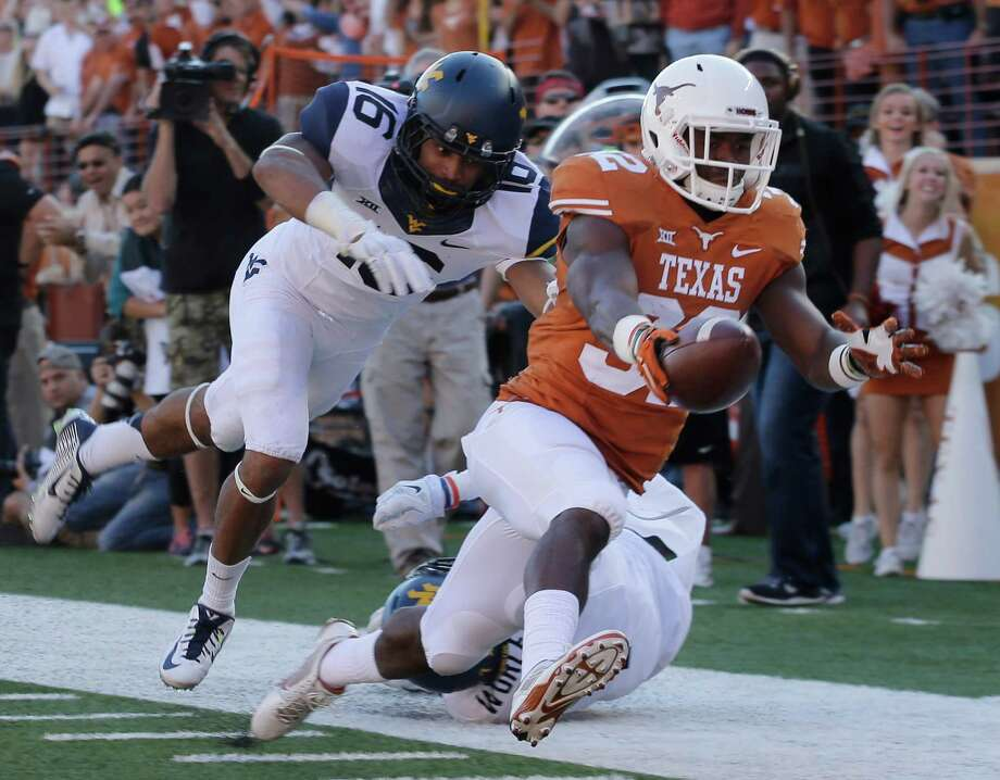 Texas' Johnathan Gray stretches to complete a 39-yard touchdown run in the second quarter with West Virginia's Terrell Chestnut in pursuit. Photo: Eric Gay, STF / AP