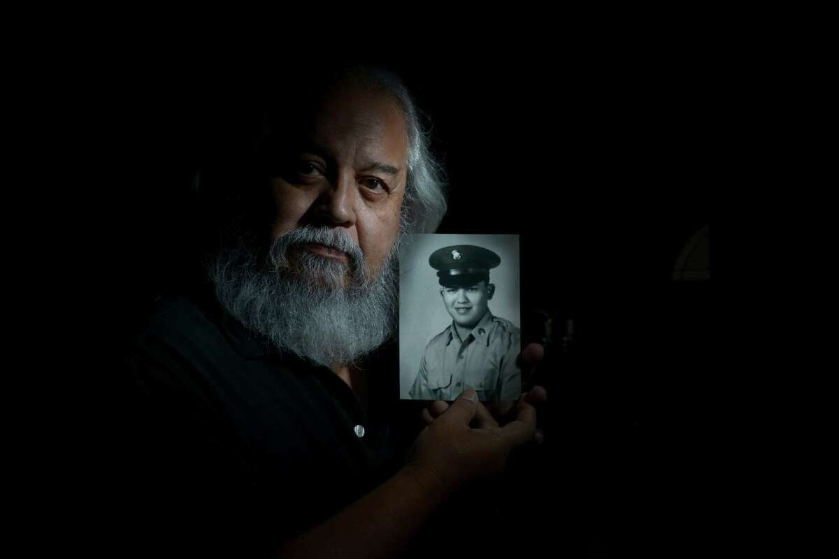 Guadalupe Lucio holds a portrait of himself when he was in the army. He served in Vietnam. He was photographed on Oct. 27, 2014.