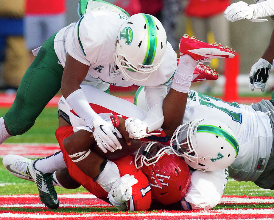 A wave of Tulane tacklers, including Nico Marley, top, buries UH quarterback Greg Ward during the first half Saturday. Photo: Cody Duty, Staff / © 2014 Houston Chronicle