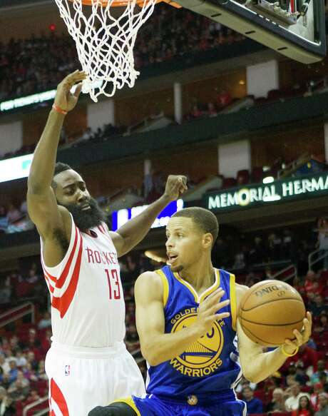 Rockets guard James Harden, left, tries to defend Warriors guard Stephen Curry during the first half Saturday night at Toyota Center. The duel of offensive stars yielded a Curry victory, as he outscored Harden 34-22 in fewer minutes and helped keep Golden State unbeaten. Photo: Cody Duty, Staff / © 2014 Houston Chronicle