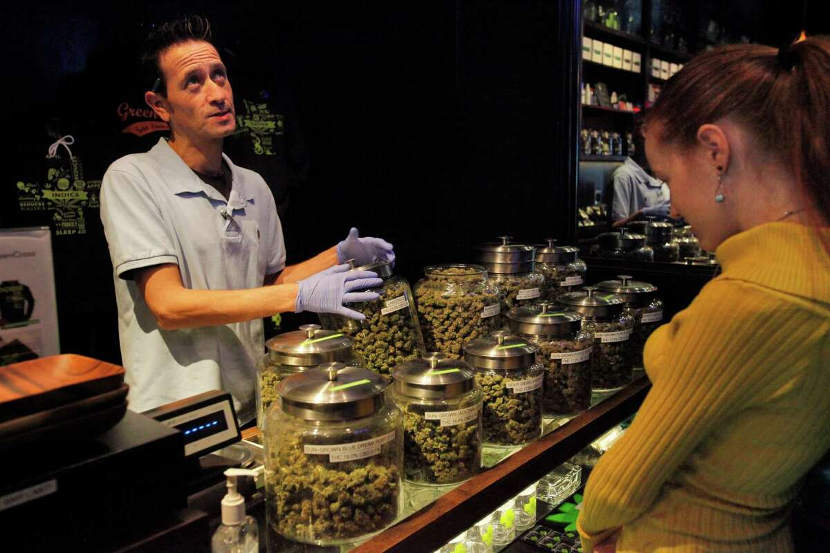 Alexis Jones, 25, right, a new patient and writer for Medical Jane, gets help from bud tender Steve Ryder at the Green Cross medical marijuana dispensary in San Francisco.