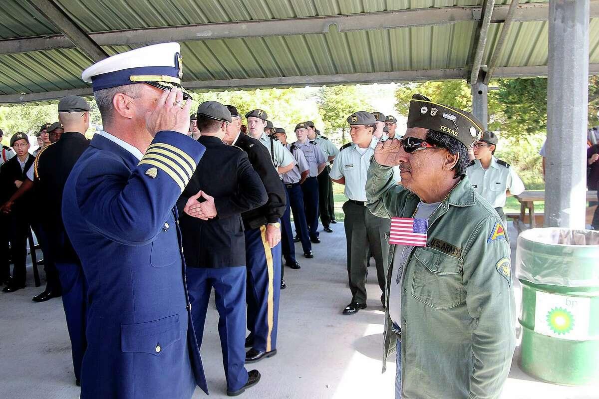 Captain Brett Millican (Coast Gaurd, CO Coast Gaurd Base Galveston), Coast Guard Capt. Brett Millican, commanding officer of the Galveston Coast Guard base, salutes Vietnam veteran Rudolph Garcia of Texas City during the Veterans Day ceremony at Dickinson VFW Post 6378.