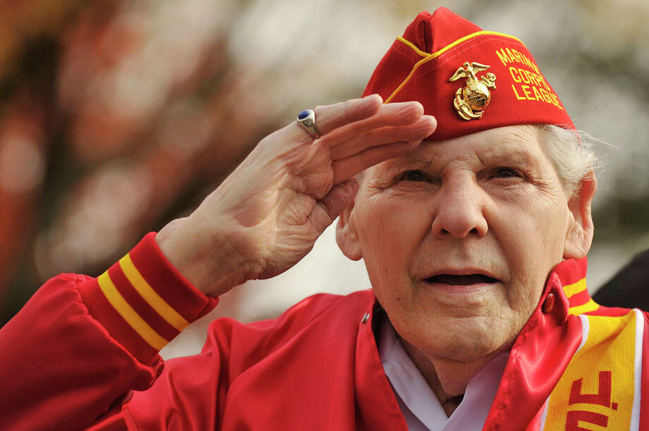 Retired Marine Corps Master Sgt. John Geas salutes the American flag as it is raised during the Veterans Day ceremony in Veterans Park in downtown Stamford, Conn., on Sunday, Nov. 9, 2014. Geas says he was on a landing ship tank when it was disabled while attemting to land on Iwo Jima and was forced to swim ashore and spent six months fighting off the Japanese. Photo: Jason Rearick / Stamford Advocate