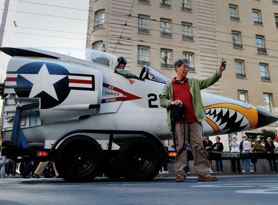 A man from the crowd steps up to take a selfie with part of an F-11 Tiger at the Veterans Day parade. Photo: Brant Ward / The Chronicle / ONLINE_YES