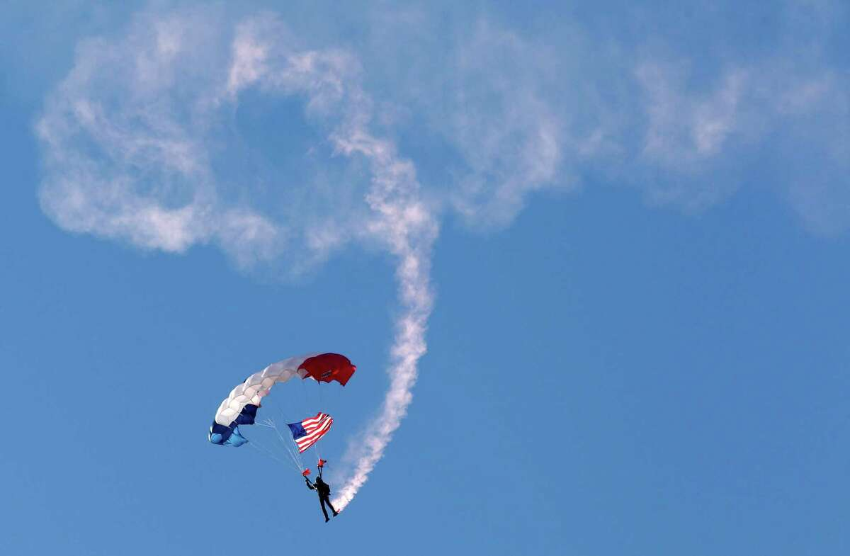 Mario Rivera, a retired Army veteran, carries the U.S. flag during the Veteran Parachute Jump Team demonstration at the annual Salute to Military Service at the Kemah Boardwalk Sunday, Nov. 9, 2014, in Kemah.